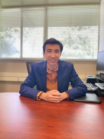 Alex Wong sits at his desk in his office.