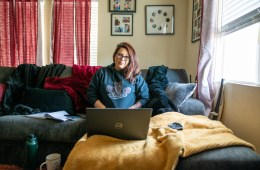 Irene Echavarria sits on her couch with her laptop open in front of her.