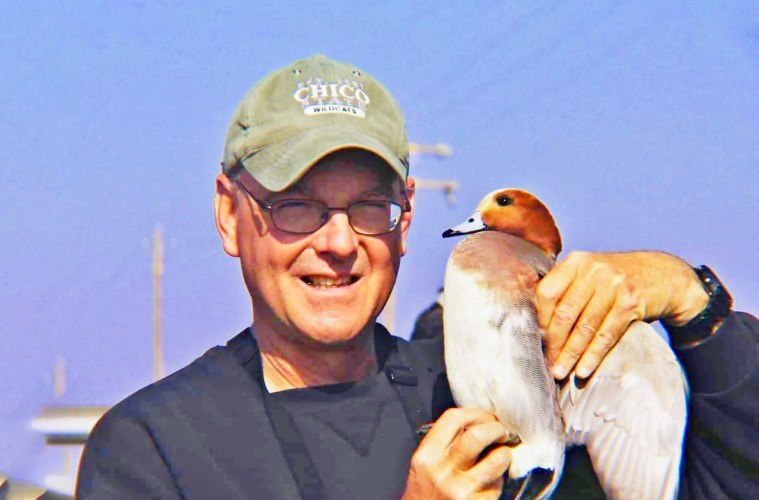 Jay Bogiatto holds a bird in his hands.