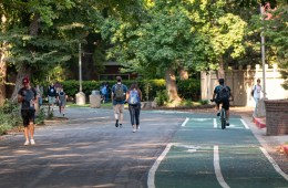 Students walk and ride bicycles on a college campus.