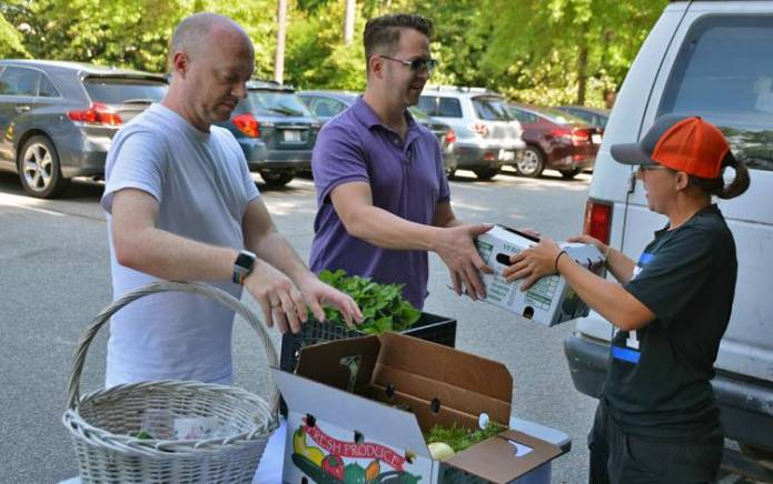 Emily McGinty, assistant program manager for Duke Campus Farm, hands Wickliffe Shreve, left, and Craig Shreve, right, their box at Sarah P. Duke Gardens.