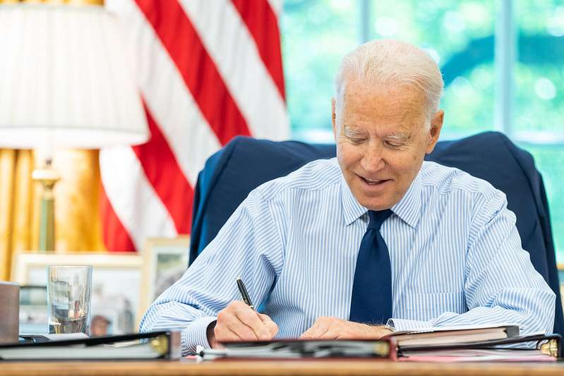 President Joe Biden talks on the phone with U.S. Senator Tom Carper, D-Del., during congressional call time on Friday, July 16, 2021, in the Oval Office of the White House. (Official White House Photo by Adam Schultz)