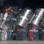 Riot police cover themselves with their shields as protesters throw stones during a protest against agricultural and trade policies in Bogota