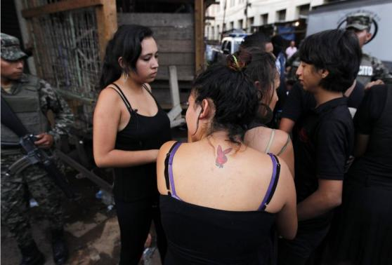 Family members and friends hug while mourning for a young man who was shot amidst what local media claimed are accusations of extortion from vendors at a market in Tegucigalpa August 26, 2014.