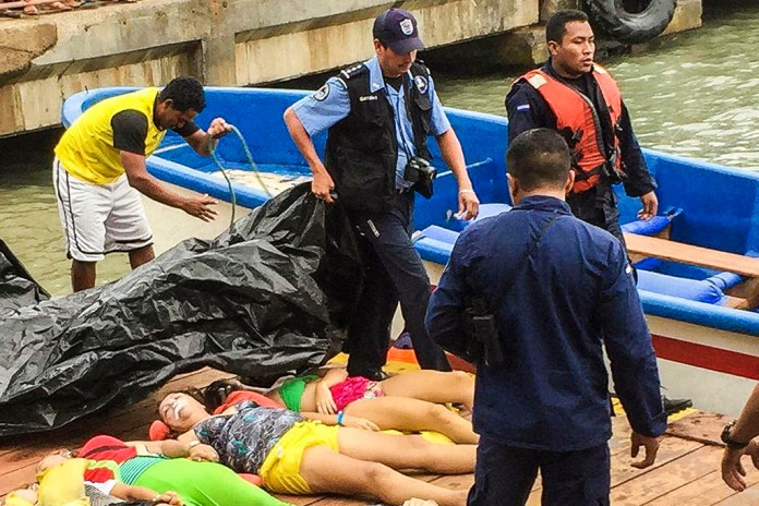 Members of the National Police and the Navy receive in the pier of Corn Island, Nicaragua, the corpses of nine Costa Rican citizens who died in a boat accident off the coast of Little Corn Island on January 23, 2016. Nine Costa Ricans were killed as four others remain missing, of 32 people who were on the boat. AFP PHOTO/STR / AFP / STR