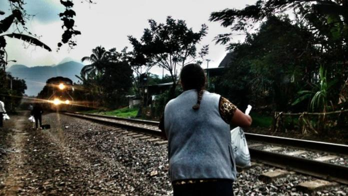 "A member of the migrant aid group ""Las Patronas"" waits for the train known as ""The Beast"", that was used by undocumented migrants to cross southern Mexico, to give them water and food. The Mexican government shut down the notorious train in August. Credit: Courtesy of the Mesoamerican Migrant Movement"