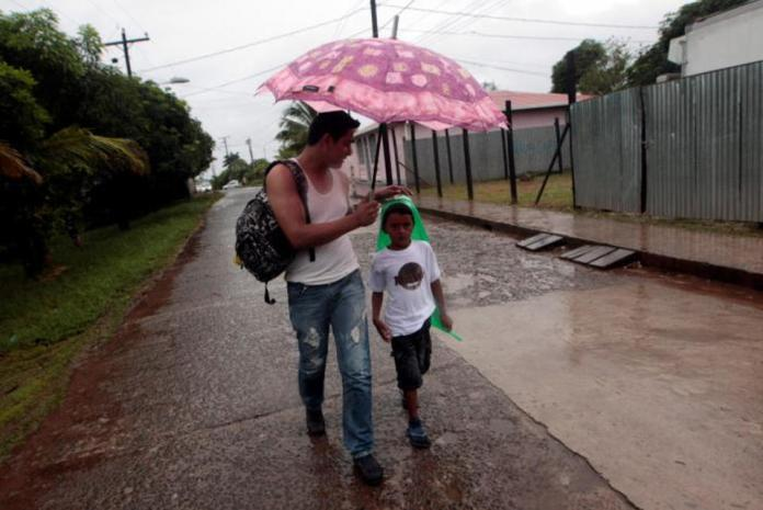 A man holds a umbrella against the rain as he walk with a boy to shelter prior to the arrival of hurricane Otto in Bluefields, Nicaragua November 24, 2016. REUTERS/Oswaldo Rivas