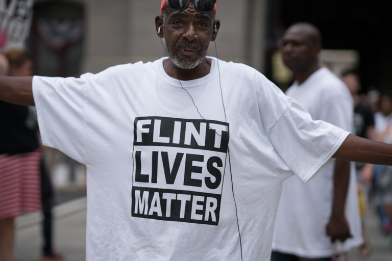"Man with shirt that reads ""Flint Lives Matter"""