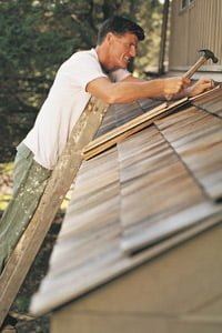 Roofer on ladder nailing shingles on roof