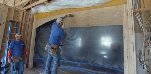 Covering doorway with plastic sheeting to keep dust out.
