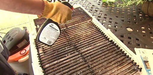Cleaning the grates on a gas grill.