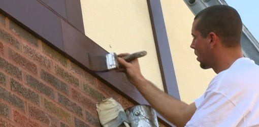 Painting trim on exterior of house.