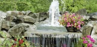 Water fountain with flowers around it