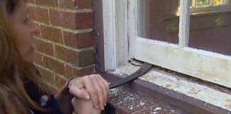 Using a flat pry bar to open a window that has been painted shut.