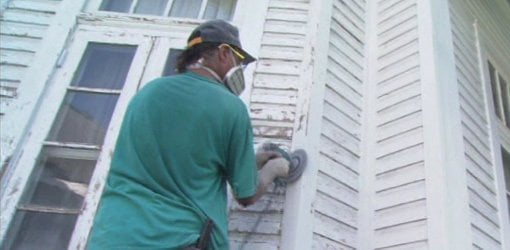 Removing loose paint on the outside of a house before painting.