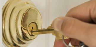 Key being inserted in deadbolt lock on door.