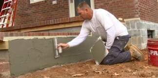 Cement being applied to concrete block foundation wall