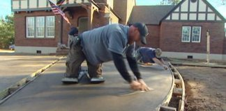 Using trowel to smooth poured concrete slab for driveway