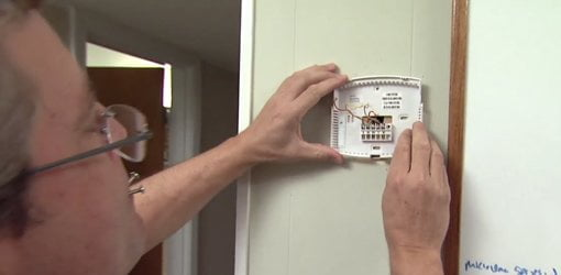 Attaching base for programmable thermostat to green painted wall.