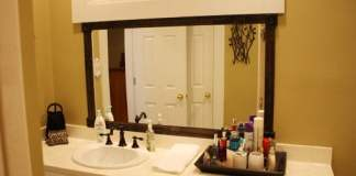 Completed stained wood frame around bathroom mirror.