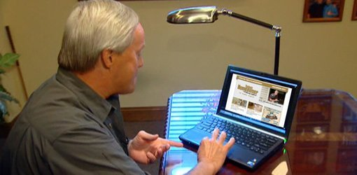 Danny Lipford looking at Tips for Today's Homeowner newsletter on laptop computer.