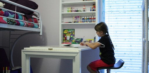 Child coloring at wall mounted folding desk.