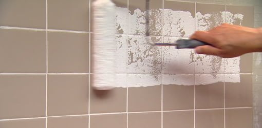 Rolling paint on a ceramic tile wall.