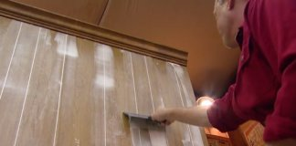 Smoothing out joint compound in paneling grooves with a drywall knife.