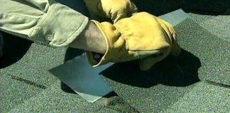Sliding metal flashing under damaged roof shingle.