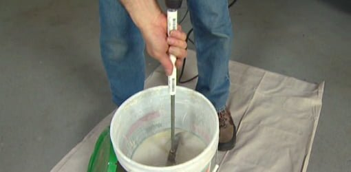 Using homemade PVC pipe paddle mixer handle to mix joint compound in bucket.