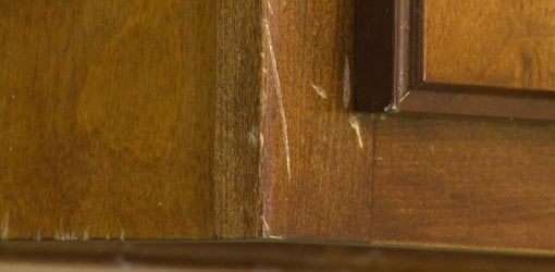 Unsightly scratches on stained wood cabinets before repair.
