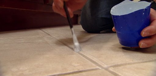 Applying a mixture of baking soda and white vinegar to clean grout lines on a tile floor.