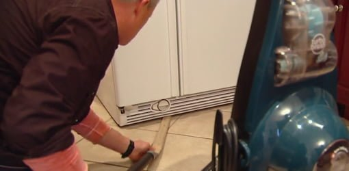 Using a vacuum cleaner and homemade wand to clean under a refrigerator.