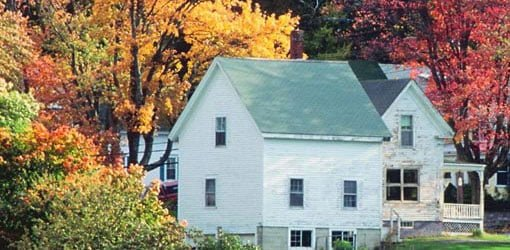 House surrounded by trees with autumn leaves.