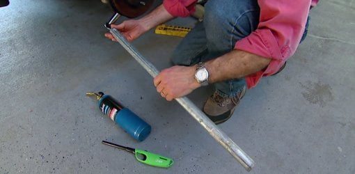 A pipe cheater bar and propane torch used to loosen stuck nuts and bolts.