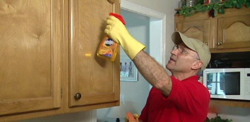 Using citrus cleaner to clean kitchen cabinets.