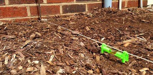 Using line level on string to measure ground slope around foundation.