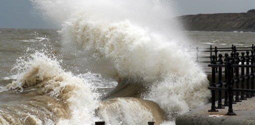 Waves breaking over seawall.