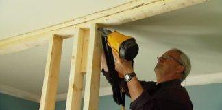 Using a pneumatic nailer to frame up an interior wall.