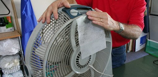 Taping a scented clothes dryer sheet to the back of a fan.