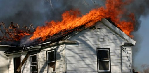Roof of house with white wood siding on fire.