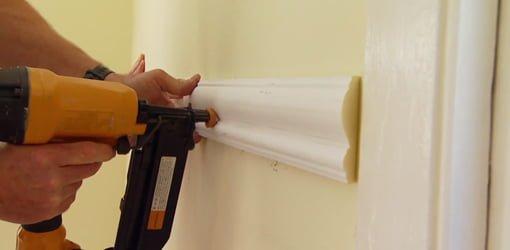 Using a nail gun to install chair rail molding on a wall.