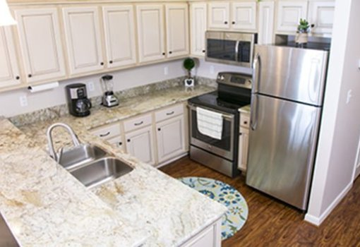 The renovated kitchen with updated cabinets, granite countertops, vinyl plank floors, and new appliances.