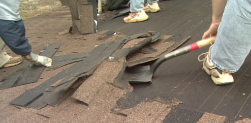 Using a shovel to remove the old roofing before installing a new roof.