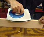 Using an iron to heat glue on veneer for banding plywood edges