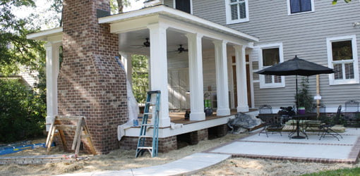 Completed back porch with fireplace, ipê wood flooring, and adjoining patio
