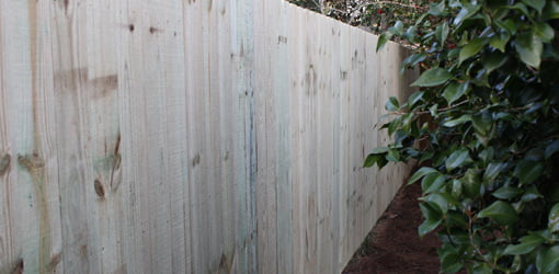 Completed pressure treated wood privacy fence.