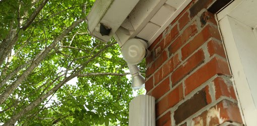 Gutter on brick house with missing downspout elbows.