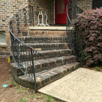 Brick steps with wrought iron railing.