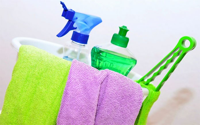A caddy of household cleaning products and rags